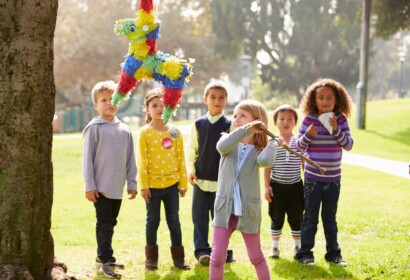 Children Hitting Pinata Hanging From A Tree At Birthday Party
