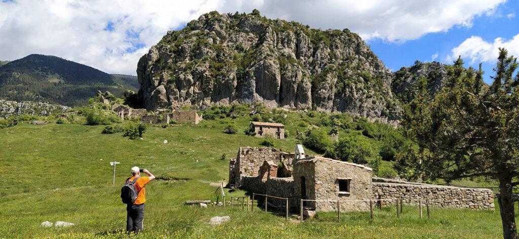 """El cementiri i el poble de Peguera, amb el gran """"Roc de Peguera"""" al darrere"""