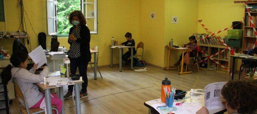 Una professora amb mascareta ajudant a fer una manualitat a una alumna de l'escola Jordi Pere Cerdà de Sallagosa (Foto: ACN).|Una professora amb mascareta i un grup d'alumnes distanciats entre ells en una de les aules de l'escola Jordi Pere Cerdà de Sallagosa (Foto: ACN).
