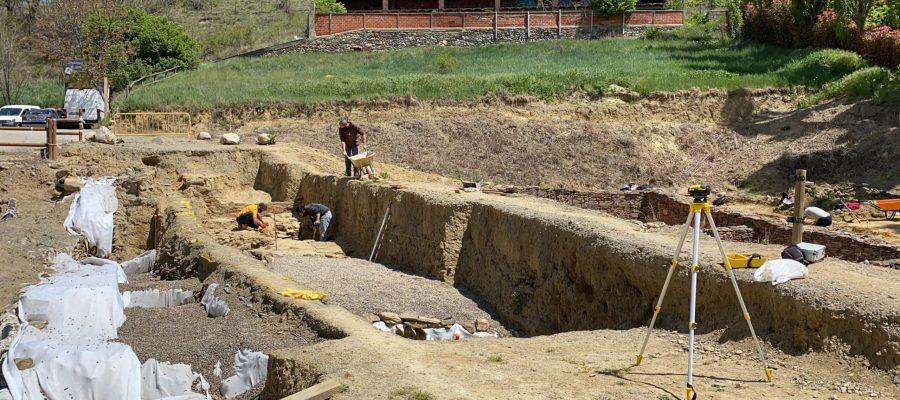 Pla obert d'una part del fòrum romà 'Iulia Libica' excavada i, al fons, un equip d'arqueòlegs treballant en aquest jaciment situat a Llívia (Cerdanya). Imatge del 20 de maig de 2021. (Horitzontal).