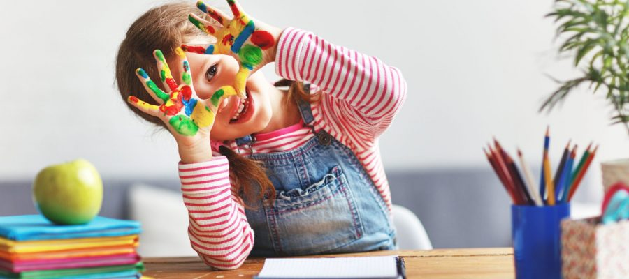 happy funny child girl draws laughing shows hands dirty with paint