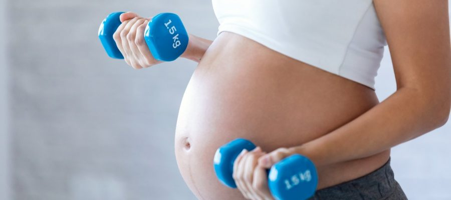 Close-up of pregnant woman doing exercise with dumbbells at home.