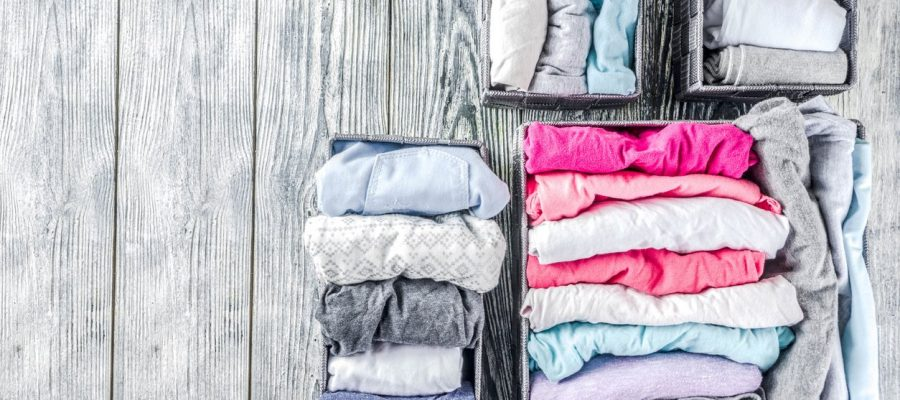 House cleaning concept. Vertical tidying up storage. Marie Kondo tidying method. Neatly folded clothes in the organizer boxes for wardrobe. Wooden background copy space above