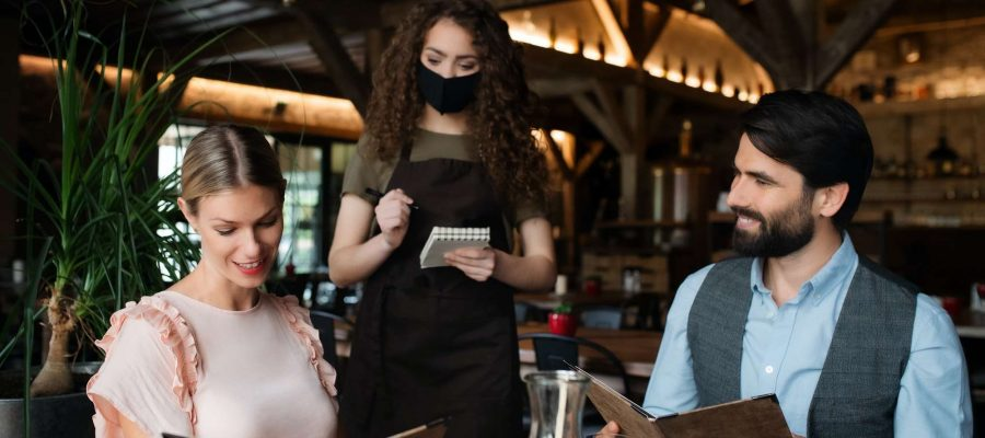 waitress-with-face-mask-serving-happy-couple-indoors-in-restaurant